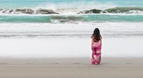 Young woman in long dress walks towards the ocean Stock Photos