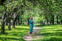 Young woman in a long dress in a wonderful spring flowering orch Stock Photography