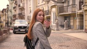 Young woman with long ginger hair walking on city street and inviting somebody to go with her, urban street background. Back view stock video