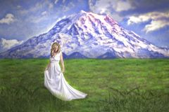 Young woman in long gown on mountain meadow. A young woman in long white gown on a green meadow with mountains on the background stock photo