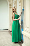 Young woman in long green dress using an automated teller machin Stock Photography