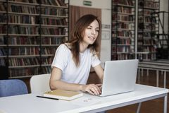 Young woman long hair analyst working at co-working office on laptop, bookshelf behind, blurred. Businesswoman learning library. Young woman long hair analyst royalty free stock photos