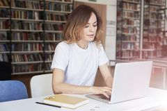 Young woman long hair analyst working at co-working office on laptop, bookshelf behind. Businesswoman learning alone in library.  royalty free stock photos
