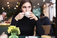 Young woman with long hair in black jersey with cup of coffee in hands having rest in cafe near window. Young woman with long hair in black jersey with cup of Stock Photo