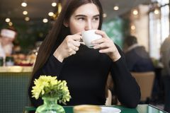 Young woman with long hair in black jersey with cup of coffee in hands having rest in cafe near window. Royalty Free Stock Photography