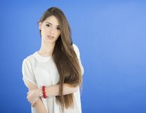 Young Woman with long Hair on blue background Royalty Free Stock Photos