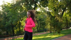 Young woman with long hair in bright pink jacket running in the sunny city park and looking in the camera. Steadicam stock video footage
