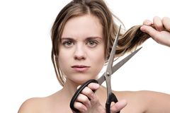 Hate how my hair looks. Young woman with long hair cutting it of with a pair of scissors having a bad hair day Stock Image