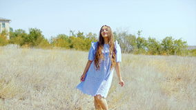A young woman with long hair is dancing in the middle of the field. stock video footage