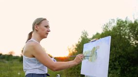A young woman with long hair that develops in the wind paints a picture on canvas, which stands on the easel. The lady. Is in an open air, she draws from life stock video footage