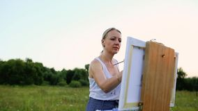 A young woman with long hair that develops in the wind paints a picture on canvas, which stands on the easel. The lady. Is in an open air, she draws from life stock video