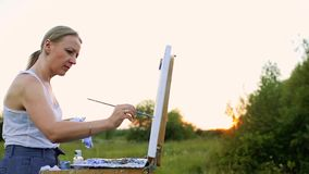 A young woman with long hair that develops in the wind paints a picture on canvas, which stands on the easel. The lady. Is in an open air, she draws from life stock footage