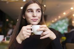 Young woman with long hair feel lonely, dreaming, drinking coffee in hands having rest in cafe near window. stock image