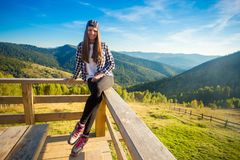 Young woman with long hair on fence of wooden terrace enjoy view of mountains. Young woman with long hair on fence of wooden terrace enjoy beautiful view of royalty free stock photos