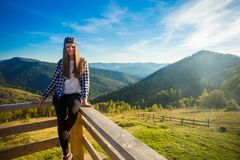 Young woman with long hair on fence of wooden terrace enjoy view of mountains. Young woman with long hair on fence of wooden terrace enjoy beautiful view of stock photo