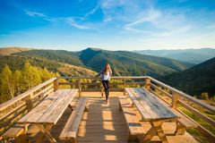 Young woman with long hair on fence of wooden terrace enjoy beautiful view of mountains stock photos