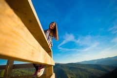 Young woman with long hair on fence of wooden terrace enjoy beautiful view. Of mountains royalty free stock photos
