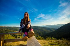 Young woman with long hair on fence of wooden terrace enjoy beautiful view. Of mountains royalty free stock image