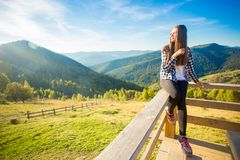 Young woman with long hair on fence of wooden terrace enjoy beautiful view. Of mountains royalty free stock photo