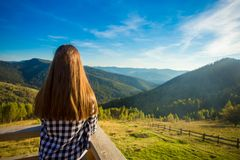 Young woman with long hair on fence of wooden terrace enjoy view of mountains. Young woman with long hair on fence of wooden terrace enjoy beautiful view of stock image