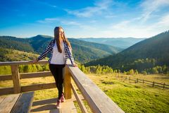 Young woman with long hair on fence of wooden terrace enjoy view of mountains. Young woman with long hair on fence of wooden terrace enjoy beautiful view of stock photography
