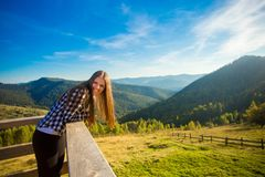 Young woman with long hair on fence of wooden terrace enjoy view of mountains. Young woman with long hair on fence of wooden terrace enjoy beautiful view of stock images