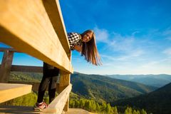 Young woman with long hair on fence of wooden terrace enjoy view of mountains. Young woman with long hair on fence of wooden terrace enjoy beautiful view of royalty free stock images