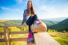 Young woman with long hair on fence of wooden terrace enjoy view of mountains. Young woman with long hair on fence of wooden terrace enjoy beautiful view of royalty free stock photo