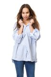 Young woman with long hair grinning and holding shirt. Portrait of a young woman with long hair grinning and holding shirt on isolated white background royalty free stock image
