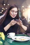 Young woman with long hair making photo by smartphone of cup of coffee, having rest in cafe near window. Stock Photo