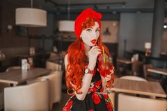 Young woman with long hair, pale skin and in rose summer dress. Beautiful redhead model drink fruit summer cocktail in cafe. royalty free stock photo