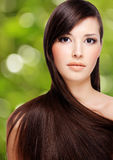 Young woman with long hair. Portrait of beautiful young woman with brown long hair over green background stock photos