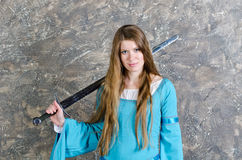 Young woman with long hair poses with sword Stock Photo