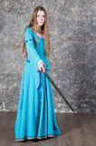 Young woman with long hair poses with sword royalty free stock photography