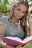 Young woman with long hair reading book in park Royalty Free Stock Photo