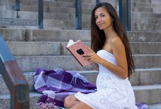 Young woman with long hair reading book sitting on stairs in urban royalty free stock image