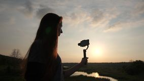 Young woman shoots video with smartphone on the stabilizer, slow motion. Young woman with long hair shoots video with smartphone on the stabilizer. Her stock video