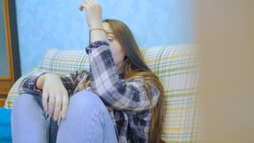 Young woman with long hair sitting on the couch and watching TV. stock footage