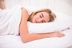 Young woman with long hair sleeping on bed in bedroom Royalty Free Stock Photography
