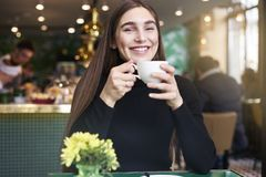 Young woman with long hair smiling, drinking cup of coffee in hands having rest in cafe near window. Stock Image