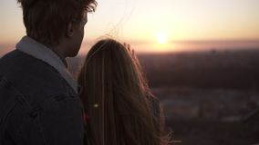 Young woman with long hair standing with her boyfriend on the roof and touching the sunlight by hand over beautiful sky stock footage