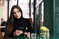 Young woman with long hair texting by mobile phone, smiling, drinking coffee having rest in cafe near window. stock photos