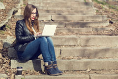 Young woman with long hair using laptop on stairs. In the park Royalty Free Stock Photos