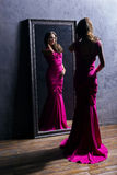 Young woman in a long pink dress standing next to a mirror Royalty Free Stock Images