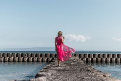 Young woman in a long red dress and with a glass of wine posing on the sea background. Bali island stock photos
