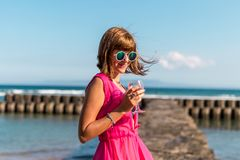 Young woman in a long red dress and with a glass of wine posing on the sea background. Bali island royalty free stock photography