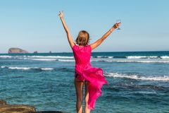 Young woman in a long red dress and with a glass of wine posing on the sea background. Bali island royalty free stock photo