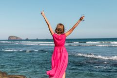 Young woman in a long red dress and with a glass of wine posing on the sea background. Bali island royalty free stock image