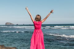 Young woman in a long red dress and with a glass of wine posing on the sea background. Bali island stock image