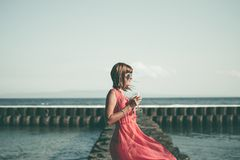 Young woman in a long red dress and with a glass of wine posing on the sea background. Bali island stock photo